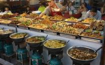Töpfe, Pfannen, Schalen und Brettchen voller leckerer thailändischer Gerichte