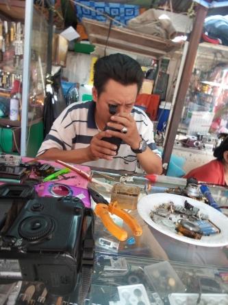 Carstens Objektiv ist kaputt - auf dem Markt in Vientiane findet man Experten, die sich das genauer ansehen - ganz schön hemdsärmelig... (bei Canon im Labor würde man sich in ein Grap legen, um sich in diesem dann umdrehen zu können...)