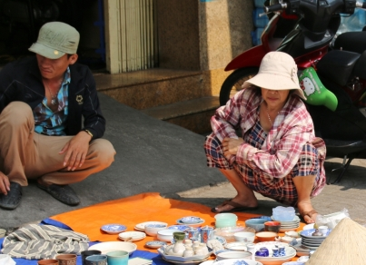 Man beachte die Hock-Haltung, ganz typisch für Vietnamesen. So verweilt man an der Straße, wenn man auf etwas oder jemanden wartet. Wir kommen mit unserem Hintern nicht so weit runter.