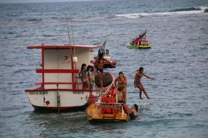 Kinder spielen im Wasser und bedienen sich dazu eines Bootes.