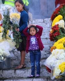 kleines Mädchen in Mitten von Opfergaben an der Kirche in Chichicastenango